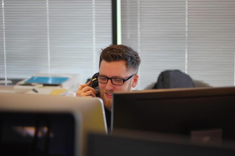 homem branco segurando telefone
